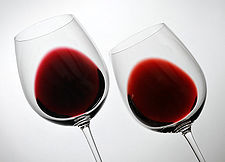 two glasses showing red wine with and without oak aging