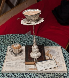 paper sculpture of a teacup on a thin spire, with a cupcake on a plate next to it, all balanced on a book