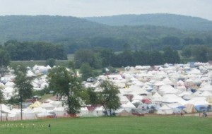 a grassy field bordered by many canvas tents