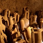 ancient Roman amphorae from Campania stacked in rows against a wall, some broken