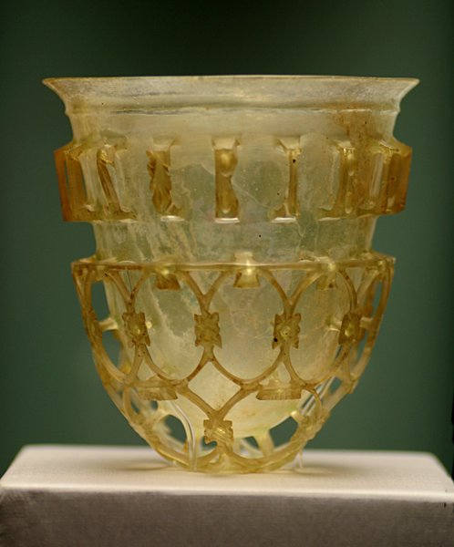 Roman glass beaker with elaborate glasswork around it