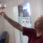 A man holding a glass of wine up to the light