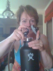 Woman holding beer tap over Hydra Flask growler with determined look on her face