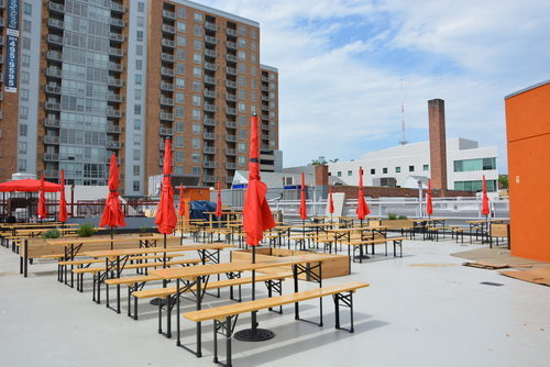 a large open space with long tables. bench seats and shade umbrellas